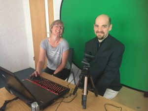 Presenters in front of green screen with laptop