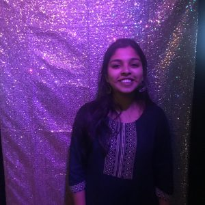 Woman standing in front of a sparkly purple curtain